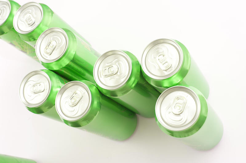 Group of green unopened aluminium soda or soft drink cans viewed from above on a white background