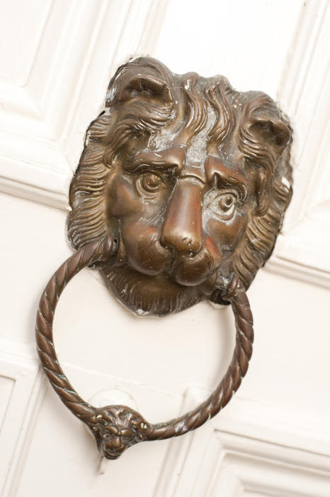 Close up Vintage Metal Lion Head Knocker on a White painted wooden front door