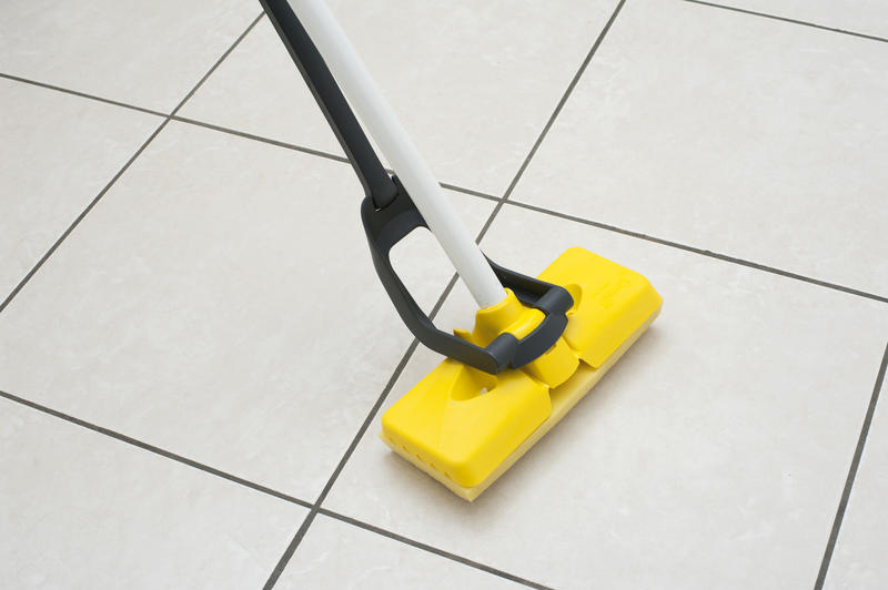 Close up Cleaning the White Tiled Floor with a Yellow Foam Rubber Mop