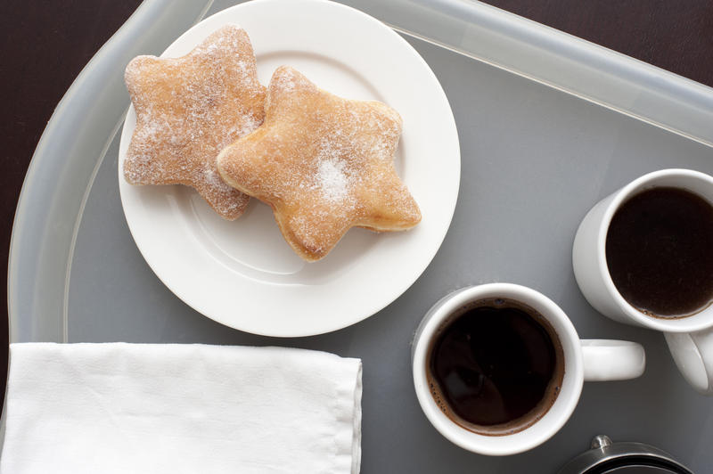 Morning coffee for two with cups of freshly made espresso coffee alongside a plate with two star shaped doughnuts, overhead view of the tray