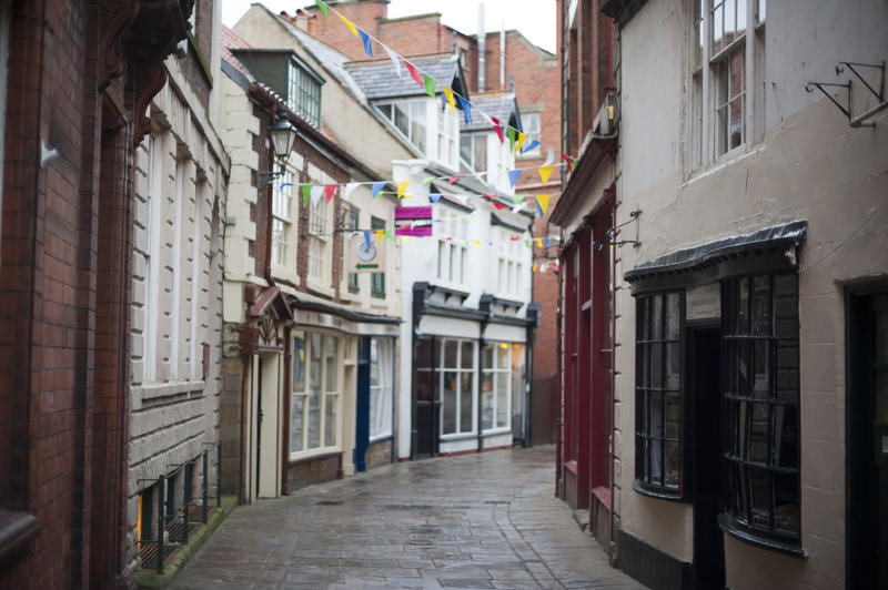 View of quaint storefronts lining the narrow cobbled street known as Grape Lane in Whitby
