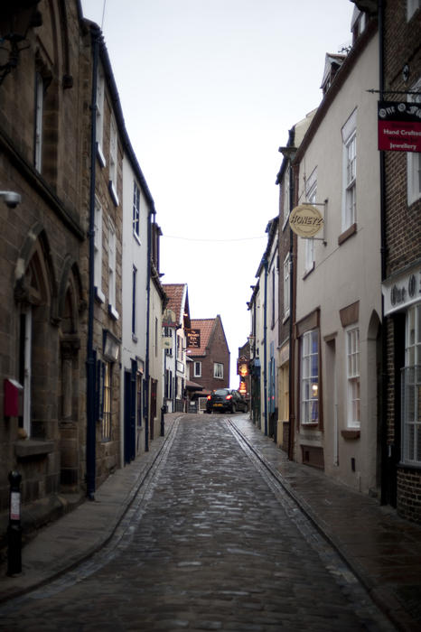 View up the historical narrow cobbled lane of Church Street in Whitby which leads from the town to the foot of the 199 steps leading up to St Mary's Church