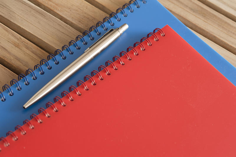 Close up Spiral Blue and Red Office Notebooks with Silver Ballpoint Pen on Top Placed on the Wooden Table.