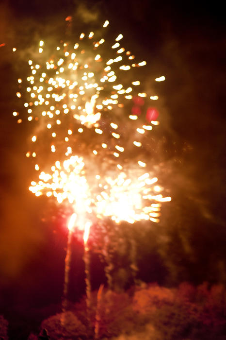 Bursts of orange fireworks lighting up a smoky night sky during a pyrotechnics display on Bonfire Night or Guy Fawkes