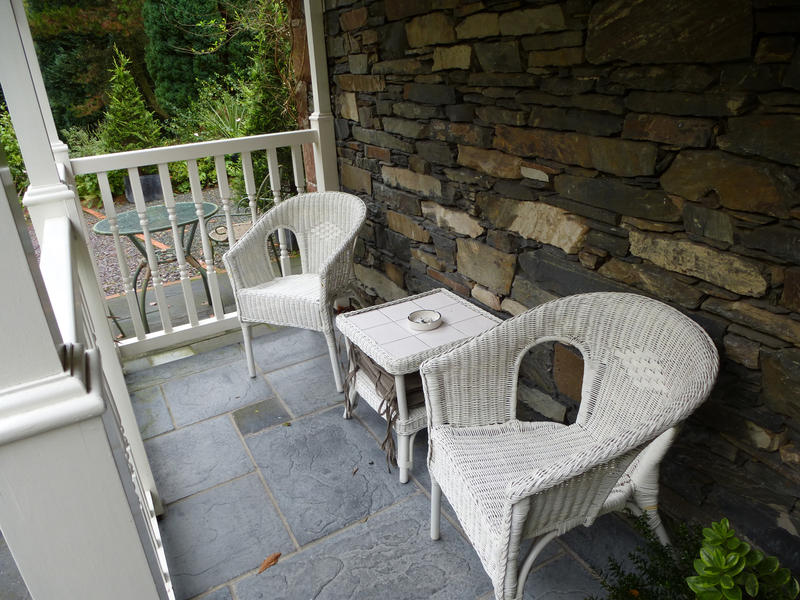 White outdoors furniture with two armchairs and a coffee table on the porch of a rustic stony house