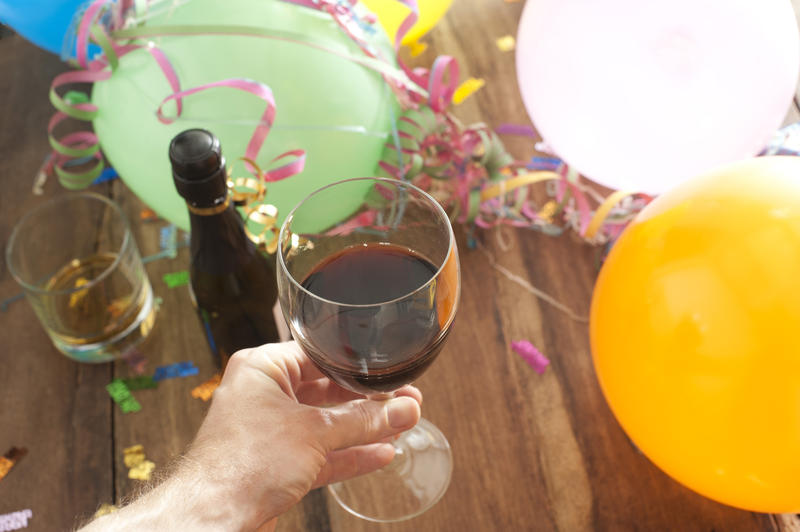 Man drinking red wine at a party holding his glass above a glass of spirits and bottle of champagne on background of colorful party balloons and streamers in a celebration concept