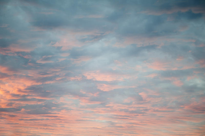 Delicate diffuse pink sunset lighting up a heavy cloud cover from below as the sun sinks below the horizon in a cloudscape and nature background