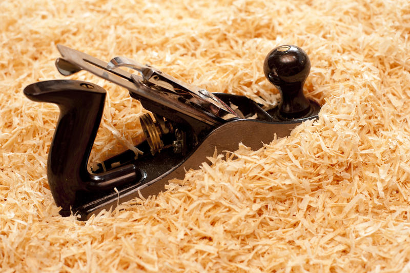 Handheld woodworking plane with an adjustable blade on a background of fresh wood shavings with copyspace