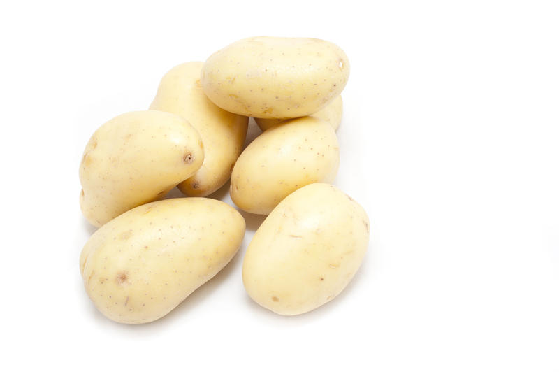 Farm fresh whole uncooked washed potatoes piled on a white background for a nutritious vegetable ingredient in cooking and vegetarian cuisine