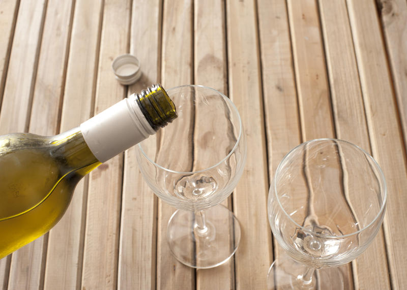 Pouring white wine from a bottle into two empty wine glasses, close up view of the top half of the bottle and glasses on a wooden slatted table with copyspace