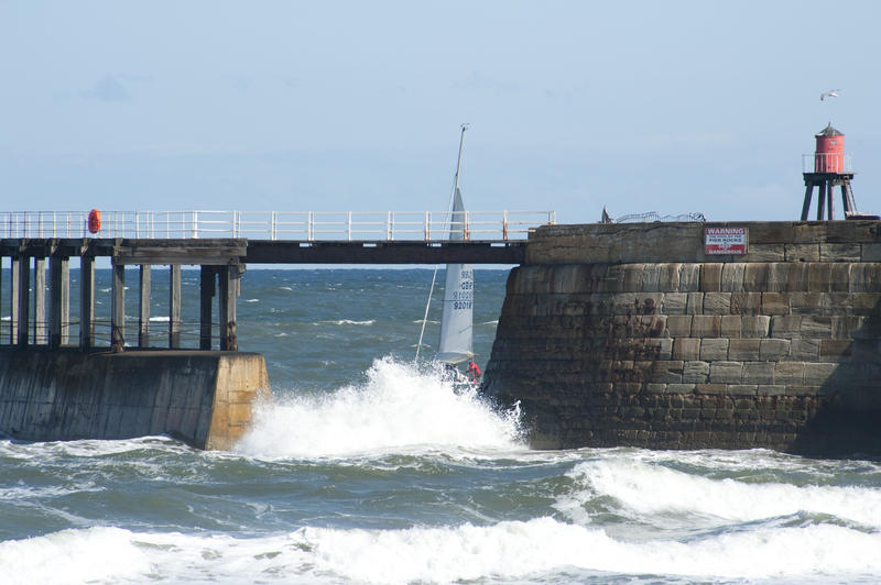 Sailing yacht passing through the sheltered waters behind the Whitby breakwater and stone pier with turbulent surf in the foreground