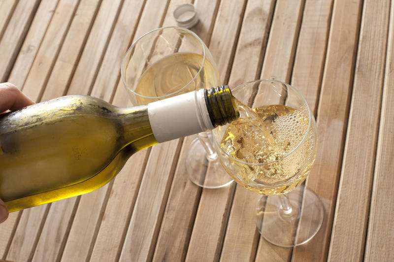 High Angle Close Up View of Hand Pouring Glasses of White Wine from Chilled Green Wine Bottle on Wooden Picnic Table