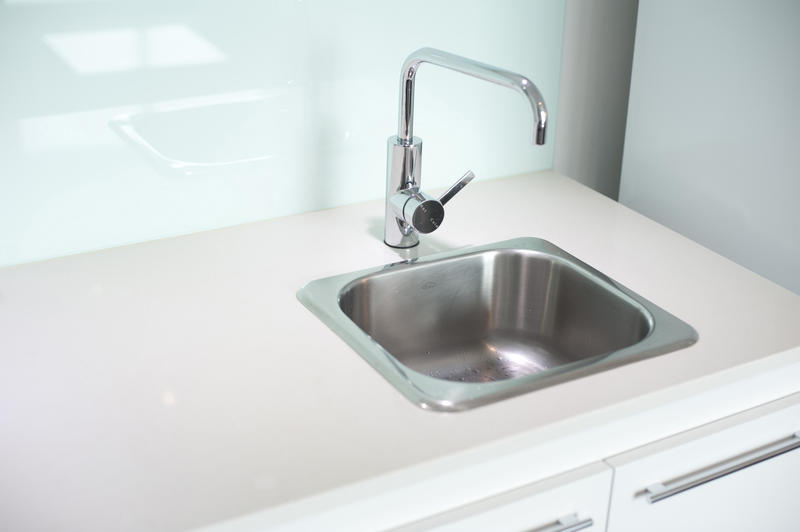 Stainless steel sink and faucet in a white kitchen cabinet with a clean empty counter alongside