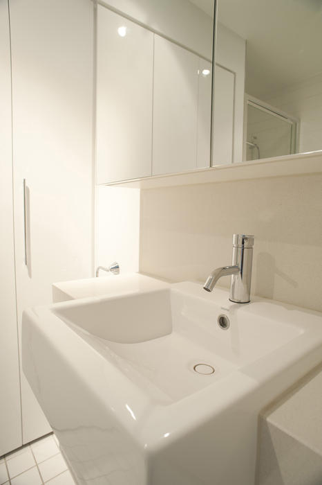 Plain white rectangular ceramic hand basin in a monochrome white bathroom with mirror and cabinets