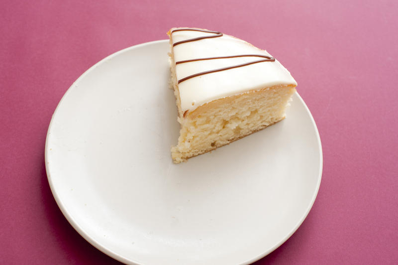 Single slice of freshly baked tasty cake with decorative icing on a plate over a deep pink background , high angle view