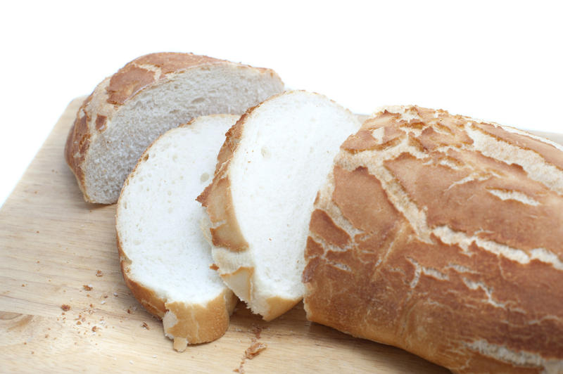 Sliced crispy freshly baked white bread baguette or roll on a bread board, close up view over white with copyspace