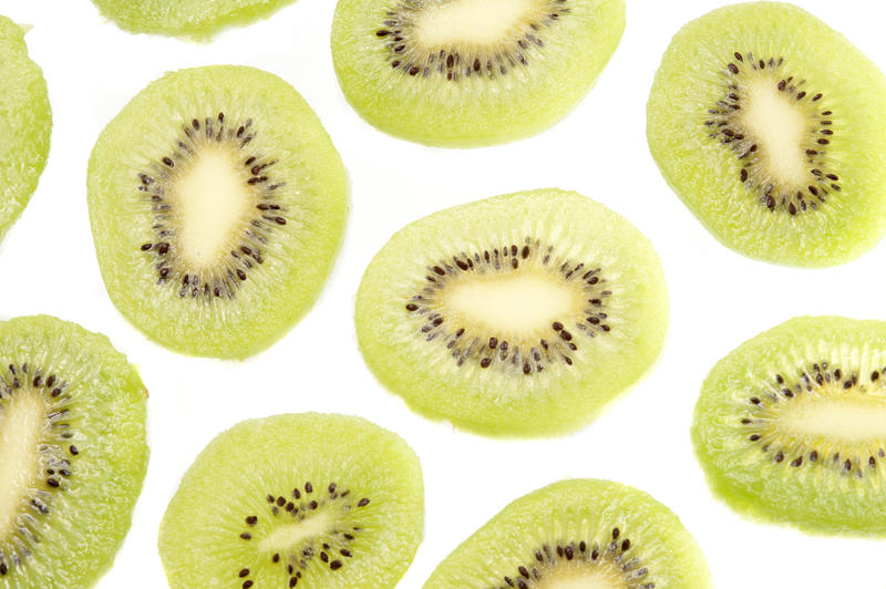 Pattern of fresh kiwifruit slices on a white background in a random arrangement showing the juicy green flesh and ring of pips
