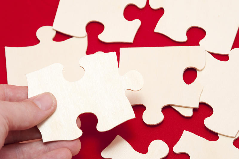 Man holding a jigsaw puzzle piece above several additional pieces on a red background in a problem solving concept