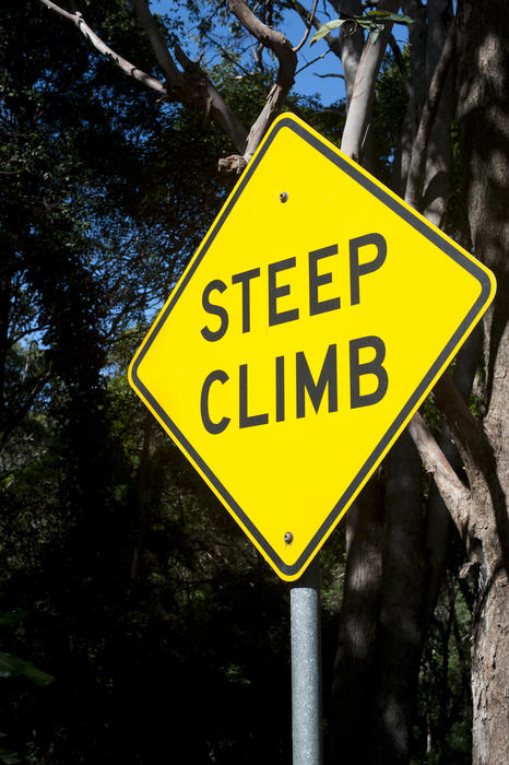 Close up Steep Climb Sign on a Yellow Diamond with Metal Bar Stand with Big Trees at the Background.