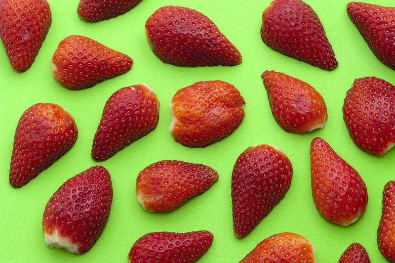 Colourful background of halved ripe red strawberries on green making a striking pattern concept for strawberry dessert