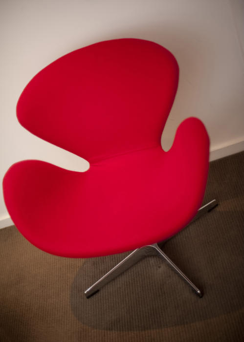 Contemporary red armchair with a funky modular design, close up high angle view on a brown carpet