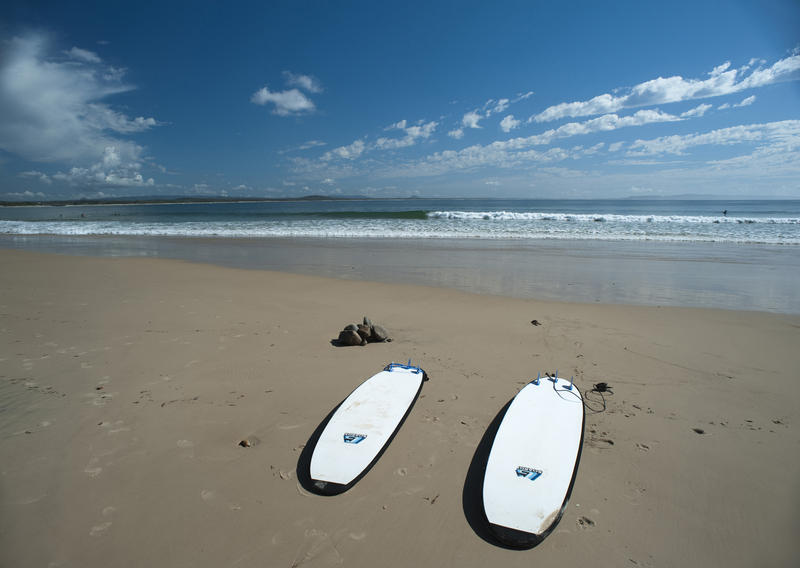 Two surfboards lying side by side on a deserted tropical beach in the summer sunshine with a calm ocean and small waves in the background