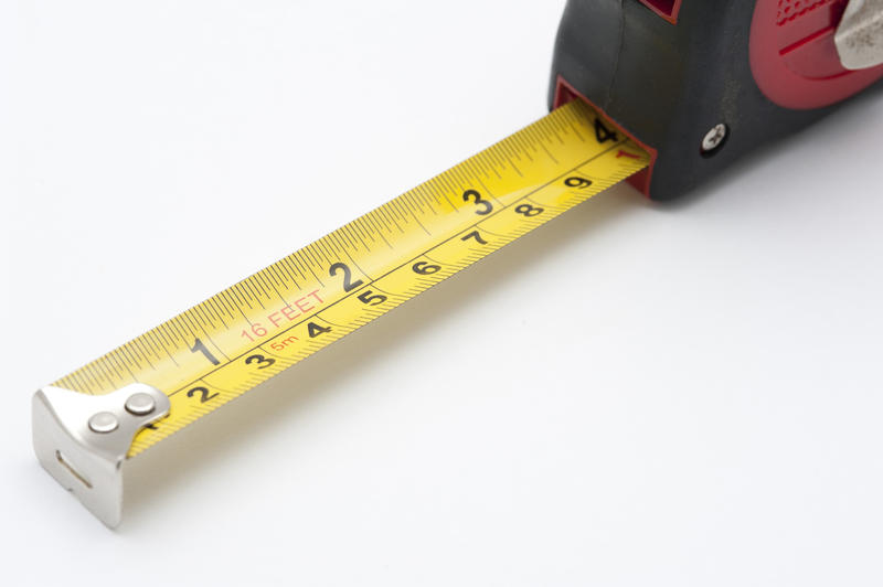 Close-up of a self-retracting yellow flexible measuring tape, on white