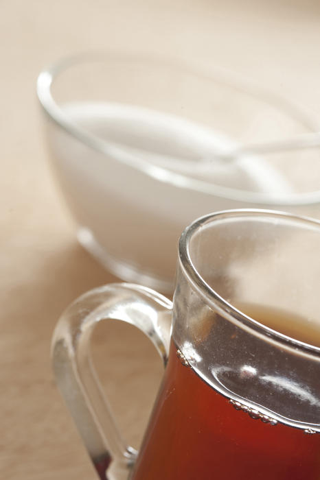 Close-up of glass of black tea and bowl of sugar