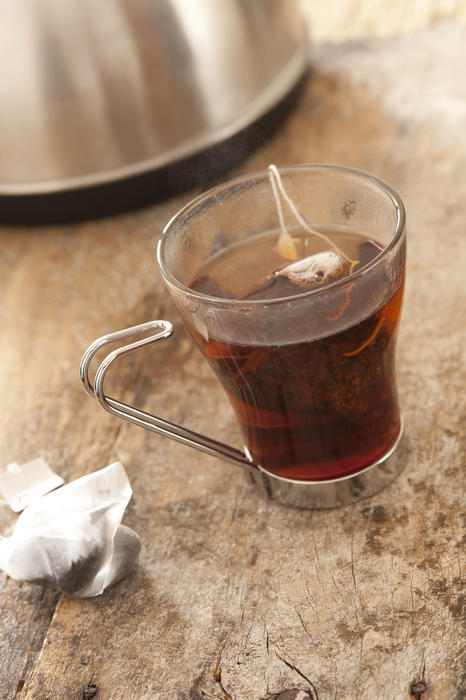 Hot cup of delicious fresh tea brewing in a rustic kitchen with a tea bag steeping in a glass mug of boiling water
