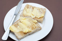 10629   Tasty Toasted Bread with Butter on White Plate