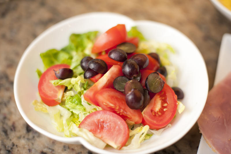 White ceramic bowl with green salad, grapes and tomatoes, high-angle close-up