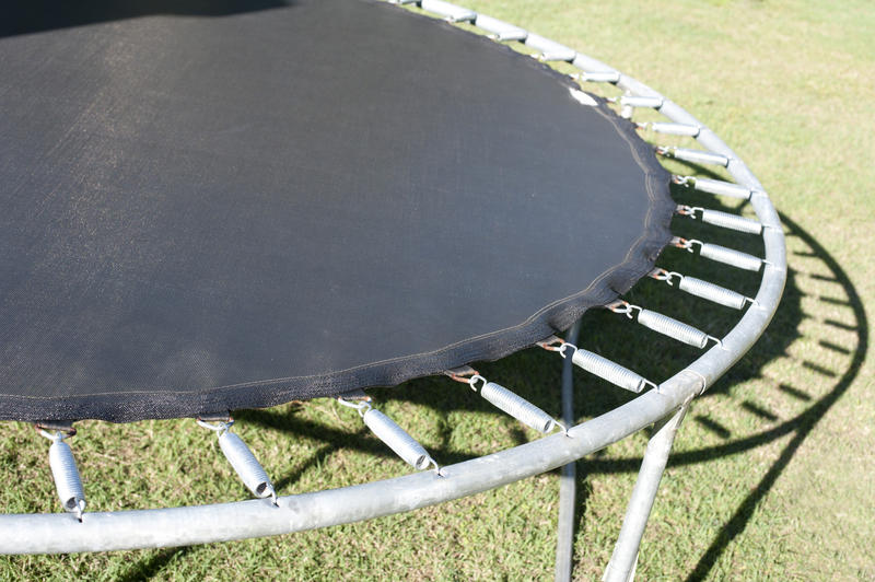 Small circular recreational trampoline with its metal frame and strong springs standing outdoors in the sunshine on the grass, close up view