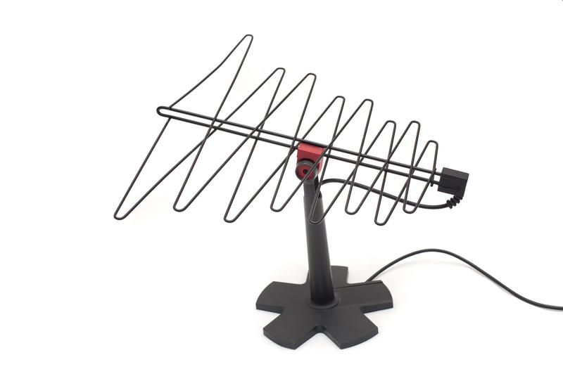 Small portable TV antenna on a stand for improving reception of television programs indoors, isolated on white