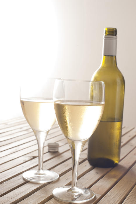 11608   Two glasses of white wine with a bottle