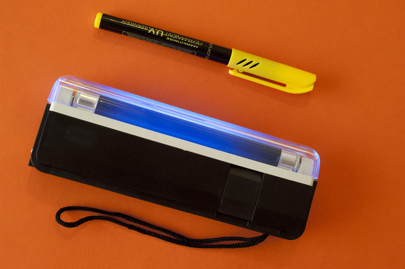Close up UV Marker Technology with Case Isolated on Orange Background