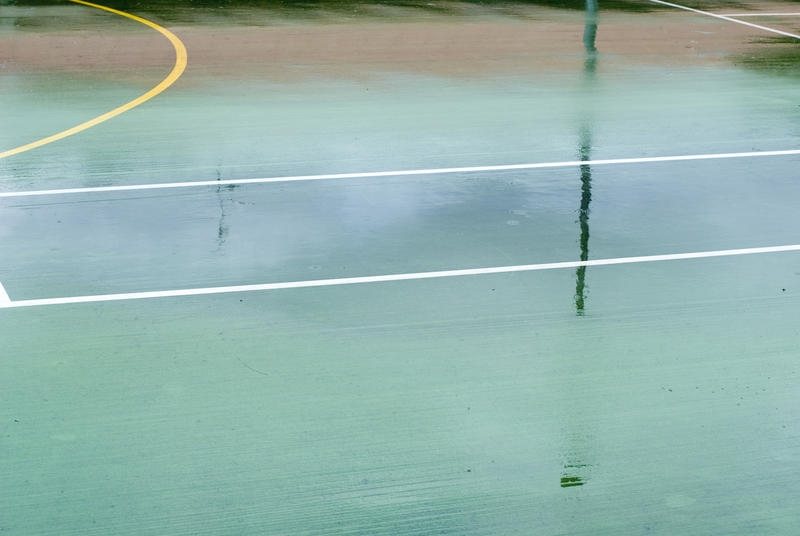 Wet all-weather outdoor sports court with line markings and a yellow circle, background texture view of the deserted court