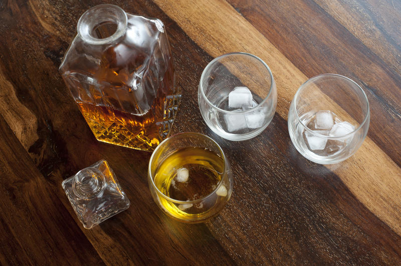 Whiskey on the rocks with an overhead view of a square decanter alongside a tumbler with whiskey and ice and two further glasses with ice. high angle view on a wooden bar counter