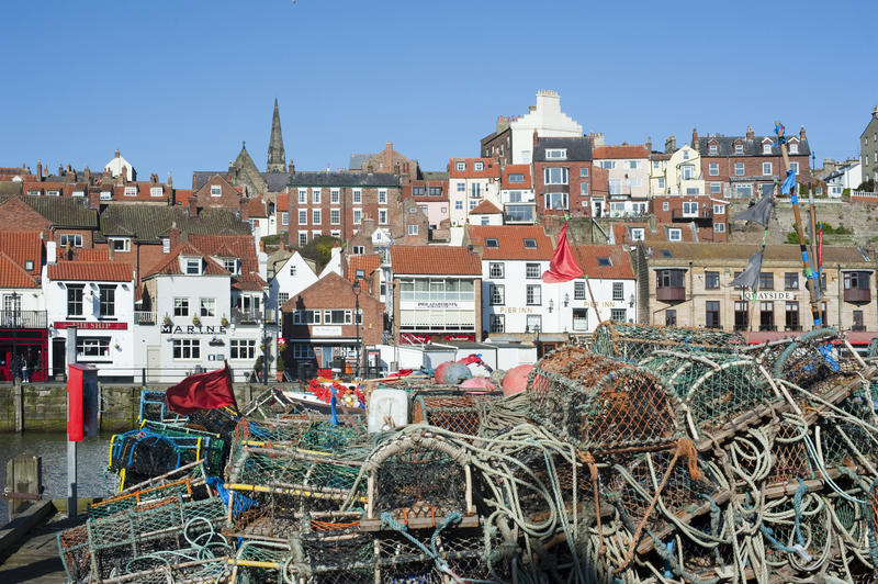 Wire mesh crab traps and lobster pots piled high on the quay at Whitby harbour overlooked by the waterfront houses and the town
