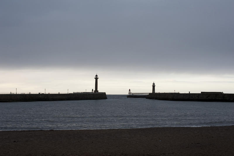 Navigation lights on stone piers and breakwaters at the entrance to Whitby harbour on the Yorkshire coast at dusk