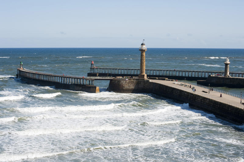Scenic view of the Whitby harbour outer breakwaters with their two guiding beacons protecting the harbour entrance from the waves and surf