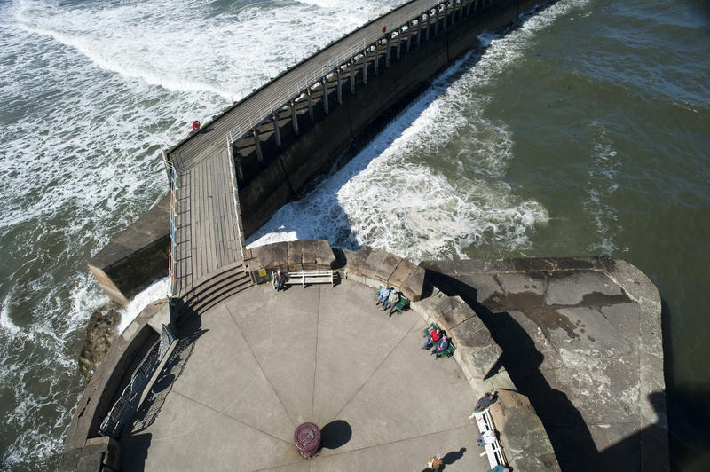 Aerial view of the historical stone West Pier in Whitby and the extended breakwater jutting out into the ocean surf at the entrance to the harbour