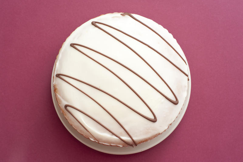Freshly backed glazed cake with a decorative zigzag pattern on the icing viewed overhead on a festive red background