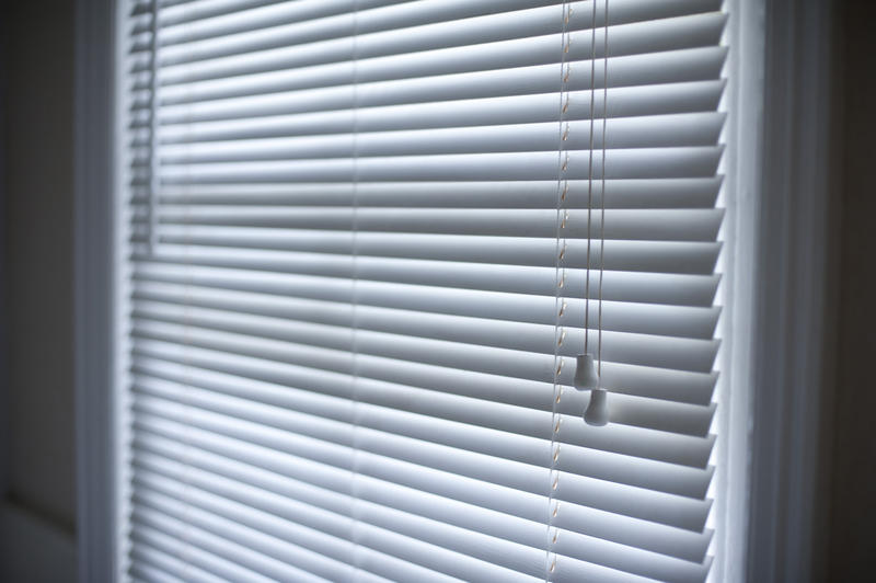 Angled view of Venetian blinds hanging in a window with the slats raised to reduce sunlight or provide privacy