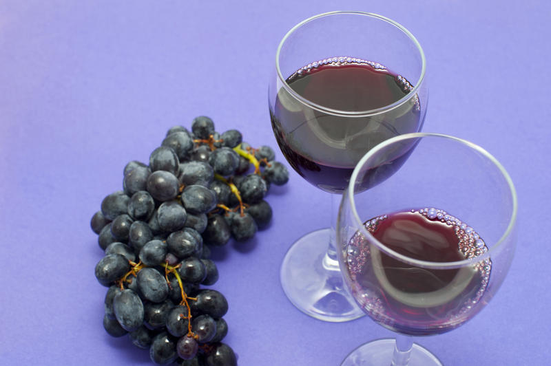 Close Up of Bunch of Dark Red Grapes on Purple Studio Background Next to Full Empty Wine Glasses with Copy Space