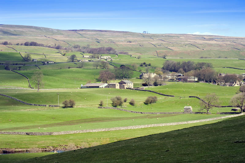 View of the gently rolling lush green hills of the Yorkshire Dales near Wensleydale with a remote farm surrrounded by pastures