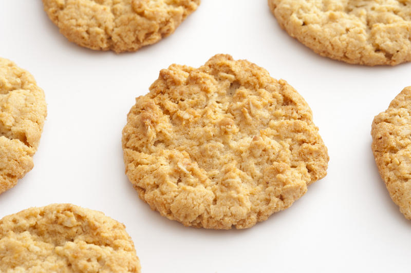 Fresh homemade Anzac biscuits with rolled oats and coconut arranged spread out on white with focus to the centre biscuit