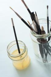 12142   Single brush in wash next to dry paintbrushes
