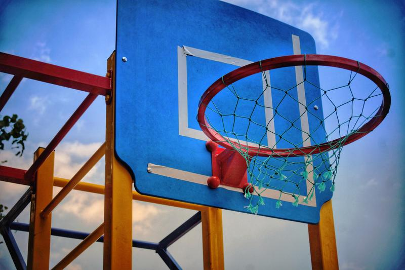 <p>Low ang view of a basketball hoop with blue backboard</p>