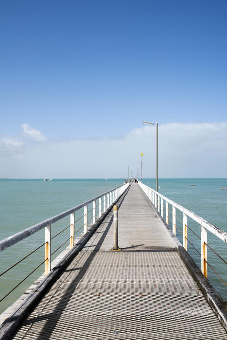 View along the deserted jetty at Beachport, Australia stretching away into the ocean on a sunny blue sky day