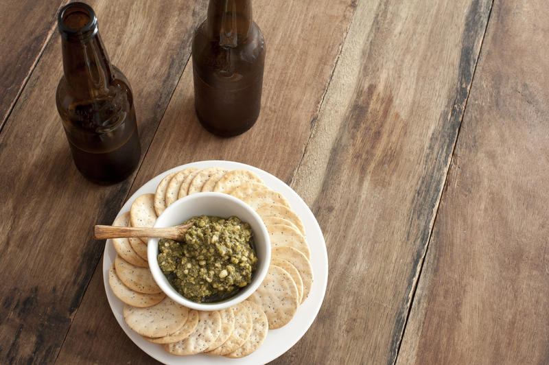 Delicious serving of green basil pesto with spoon and surrounded by water crackers beside two beer bottles
